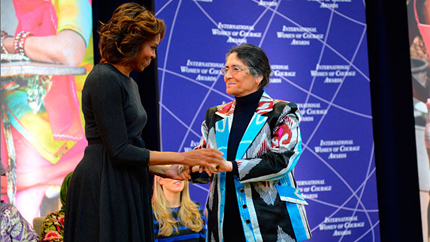 Older woman in colorful jacket shakes hands with former First Lady Michelle Obama