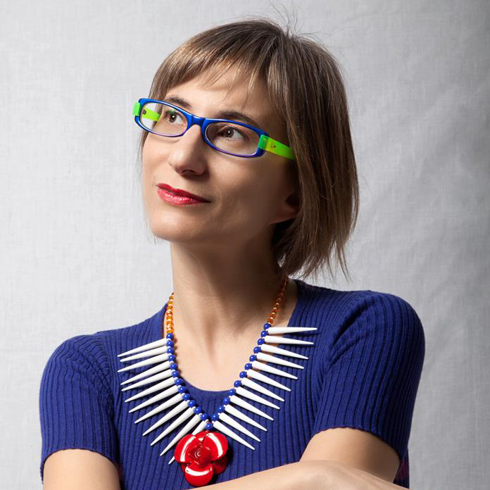 Woman wearing colorful glasses looks off to the right with a slight smile