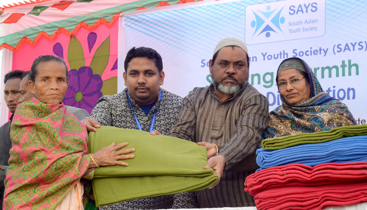 Young man holds blankets standing with group of older people