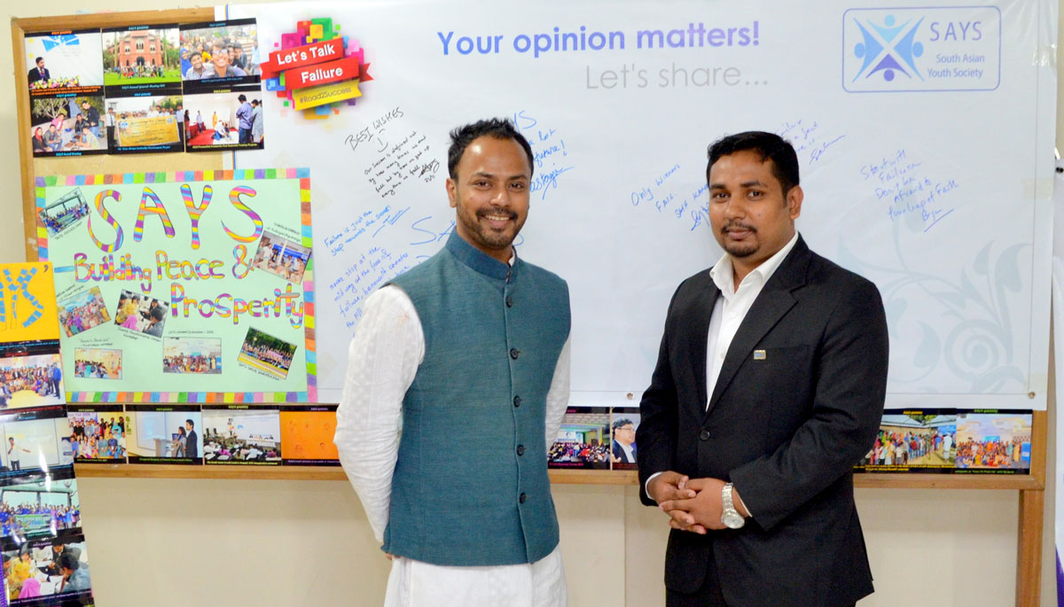 Two men standing in classroom with posters and writing on board behind them