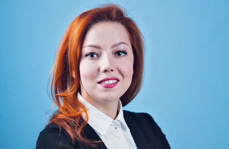 Young smiling Ukrainian woman with red hair in black blazer and white collared shirt