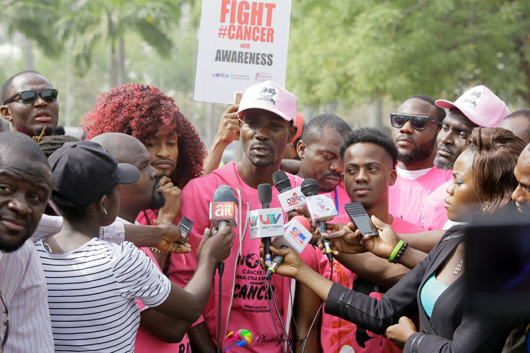 Young man stands with crowd in front of several mics and reporters appearing to interview him