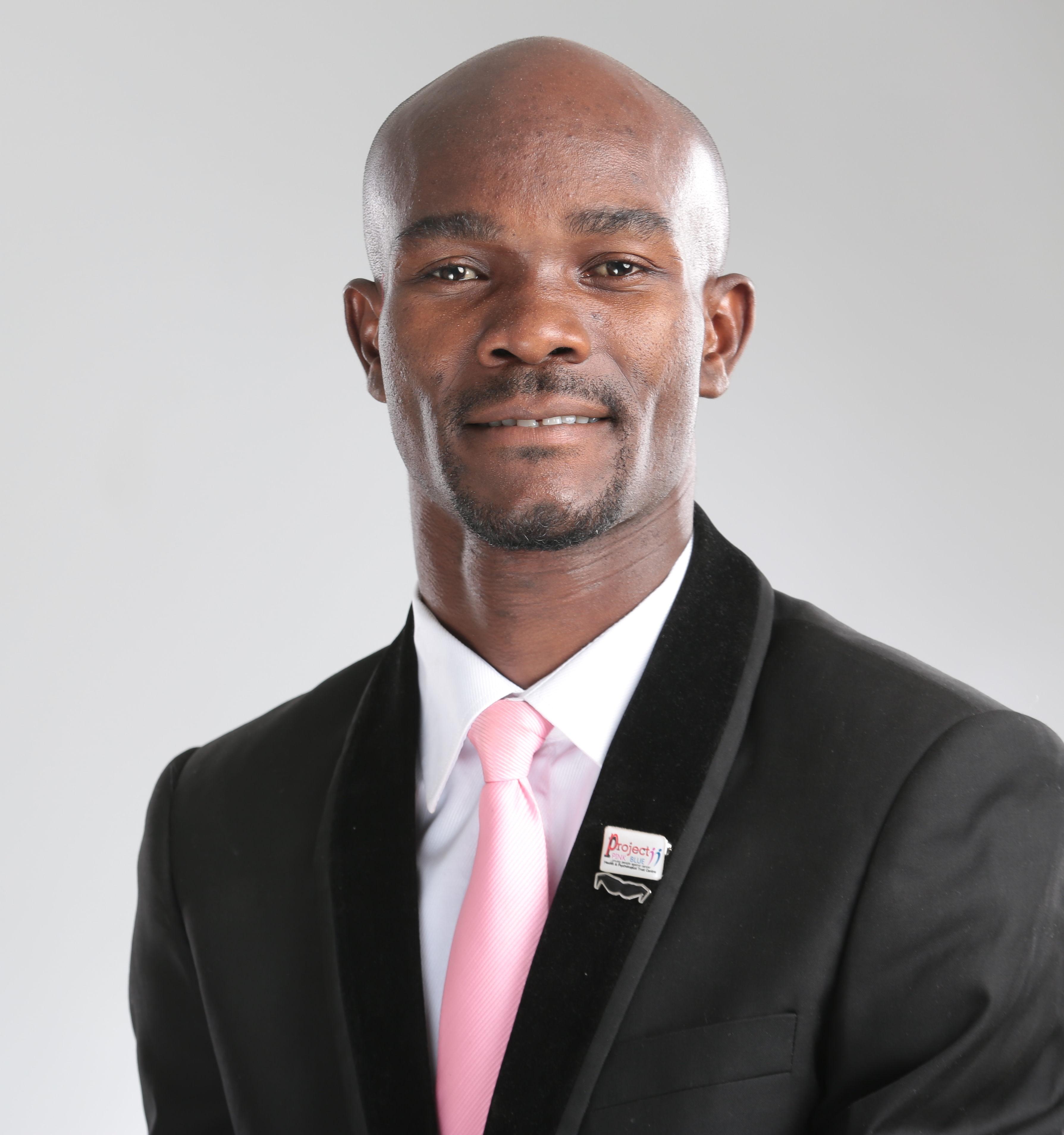 Headshot of young man wearing suit with pink tie