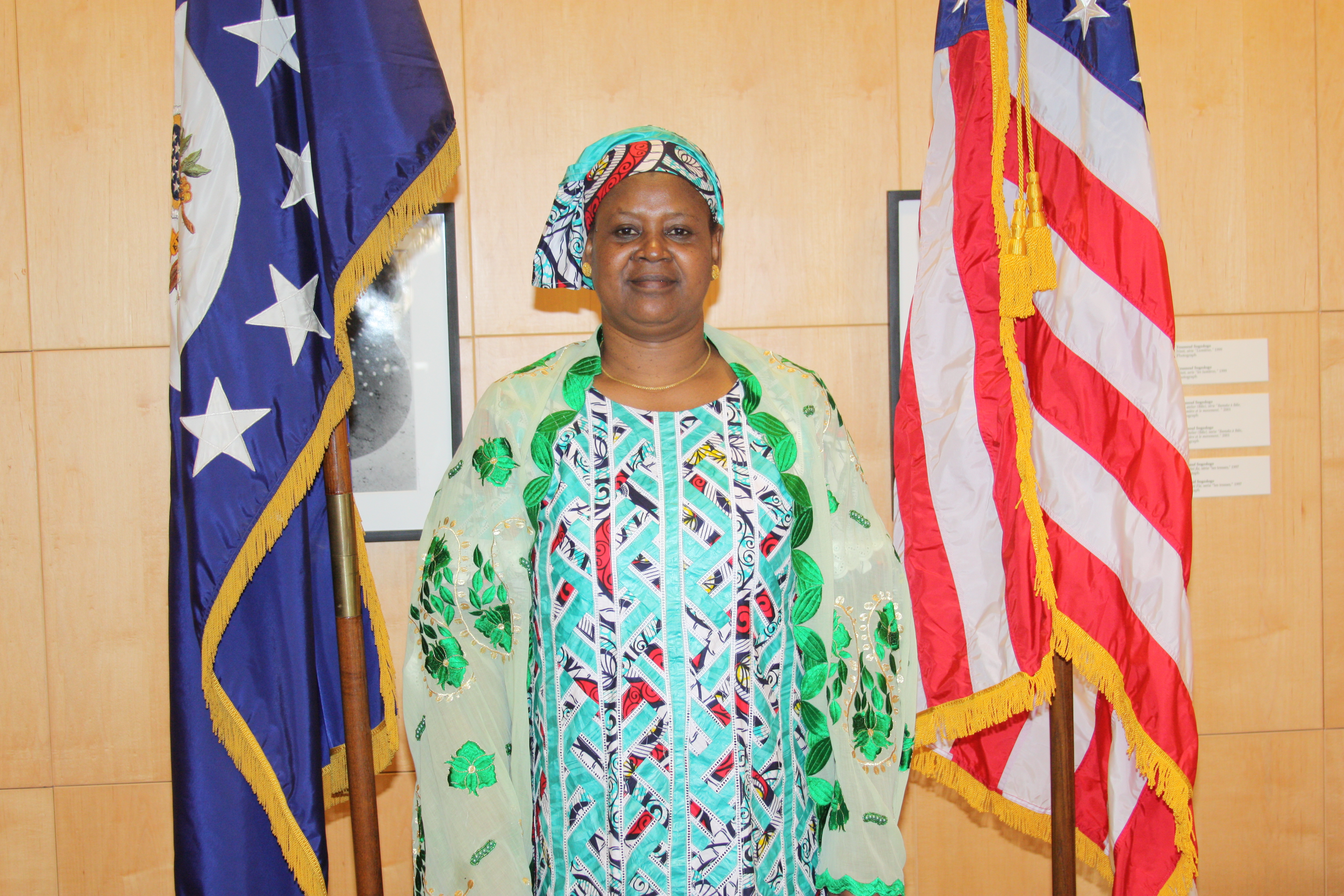 Women dressed in African print attire stands between American flag and unknown other flag