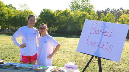"Two girls stand behind a table lined with covered plates next to a sign that says ""Baked Goods"""