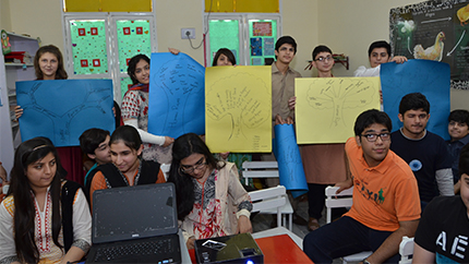 "Pakistani students hold up posters depicting ""human rights trees,"" with each branch representing an inalienable right, in Khyber Pakhtunkhwa Province on October 10, 2014."