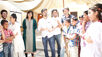 Organizers and participants enjoying a light moment during a role-playing activity at an 'Aghaaz-e-Ravvish' workshop at Mashal Model School