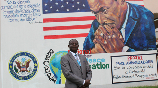 Kouadjo Hilaire, Associate Professor at University of Cocody, Abidjan, standing in front of a mural