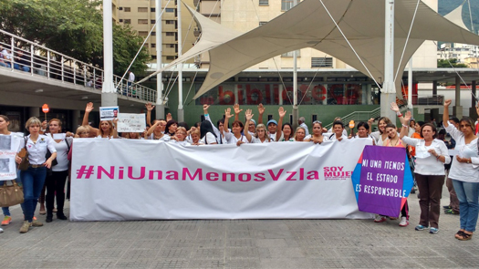 "Women holding a large banner that reads ""#NiUnaMenosVzla"" marching against gender-based violence"