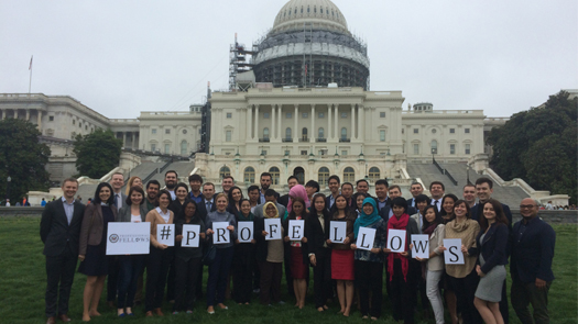 "People posing in front of the U.S. Capitol building holding signs that spell out ""#PROFELLOWS"""