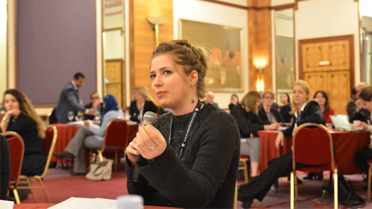 Young woman with a microphone talking in a conference room