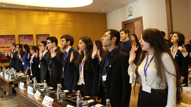 Group of professionally dressed young people holding up their right hands as if taking an oath.