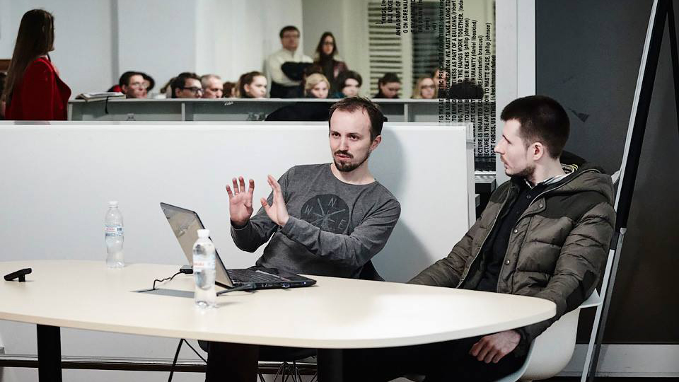 Two men talking at a table with laptop computer sitting in front of man on left