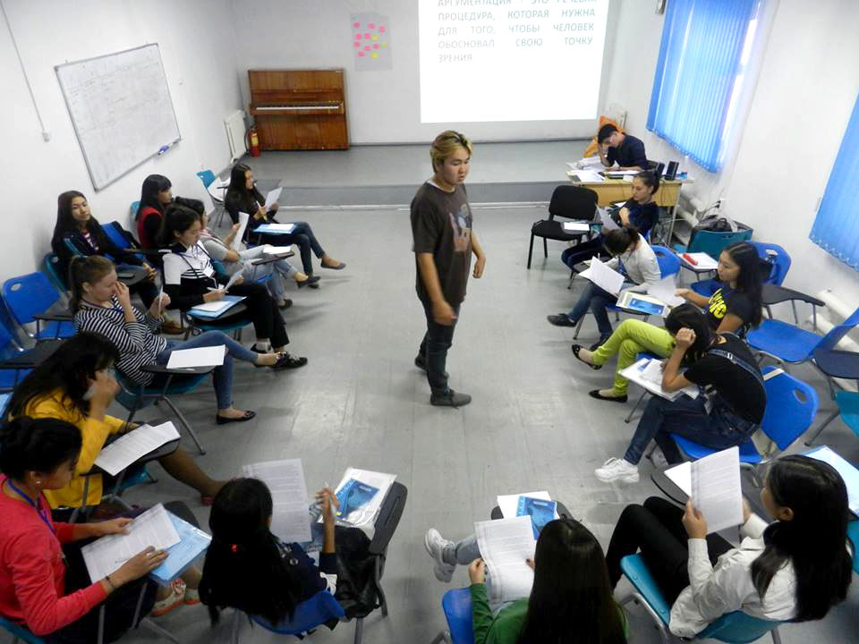 Man stands in middle of classroom surrounded by young adults sitting at desks