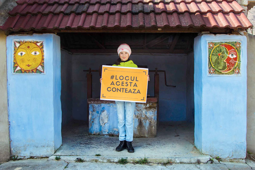 Girl stands in front of small primitive building containing well holding a sign that reads: #LOCUL ACESTA CONTEAZA