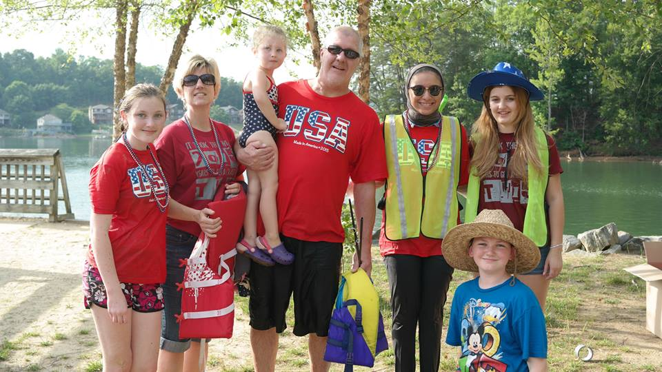 American host family with red USA shirts on standing with exchange participant