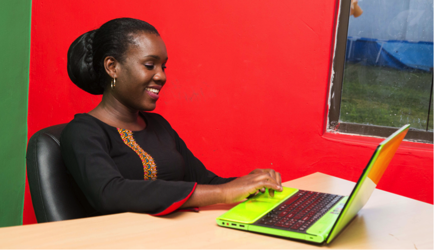 Young woman typing on laptop and smiling