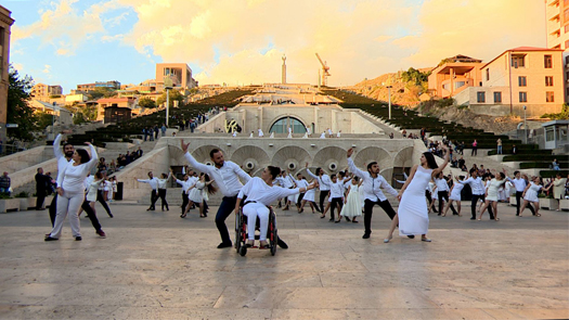 Armenian dancers dance in formation in front of grand stairs