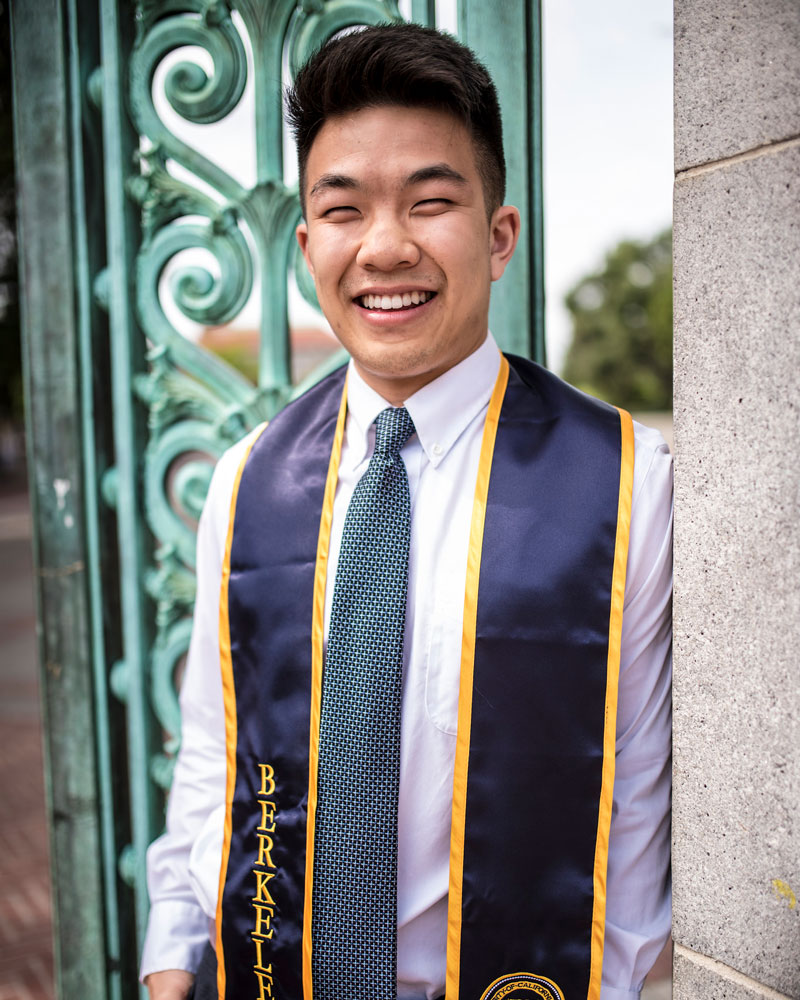 Young man wearing college sash around his neck smiling
