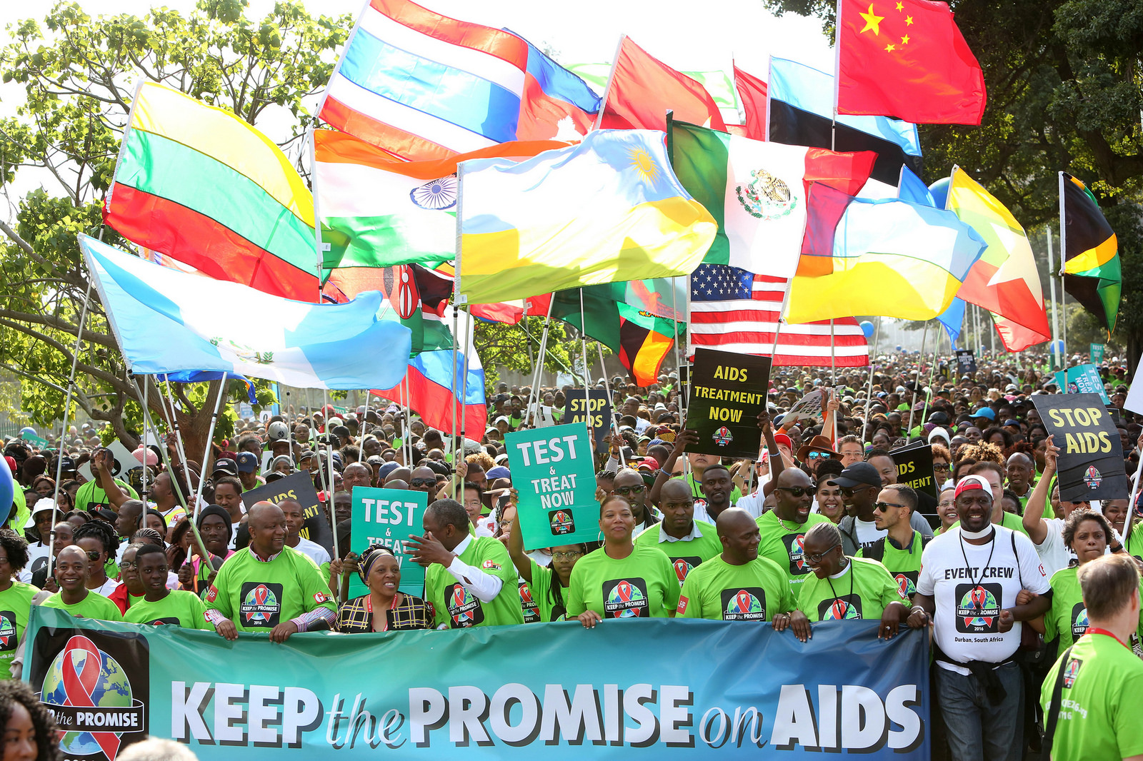 holding banner that says keep the promise on AIDS
