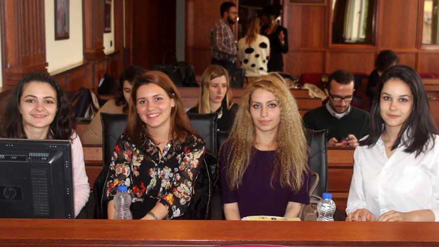 Four young women sitting at a desk in a court room