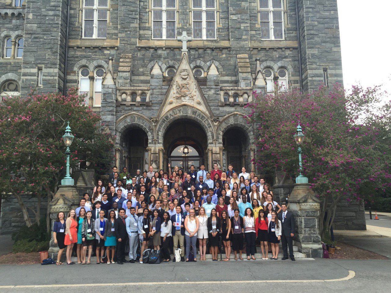Group of students pose in front of stately academic building