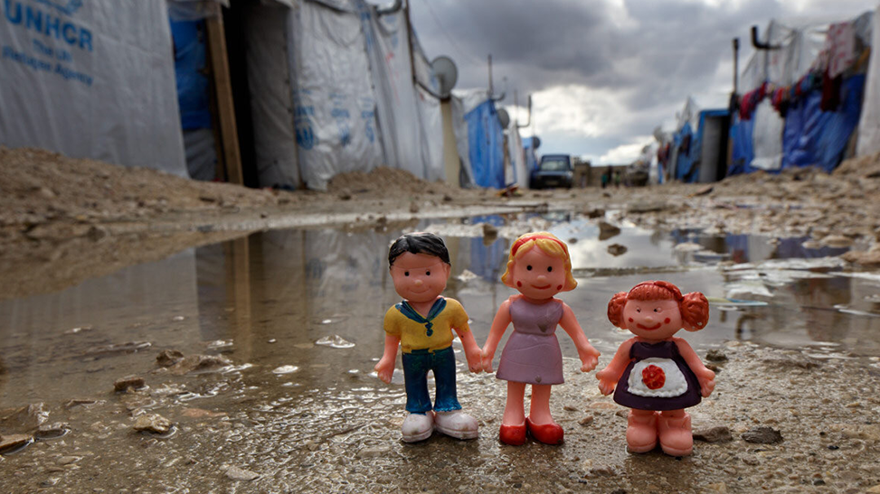 Three dolls holding hands in refugee camp