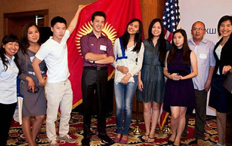 Alumni stand together beside the flags of the Kyrgyz Republic and the United States of America.