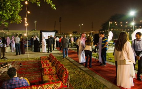 Saudi professionals standing around conversing in small groups in an outdoor patio