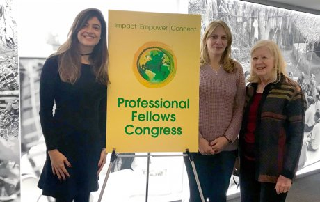 Three women stand in front of a wall lit up with an image of a rural community beside a poster that reads: Professional Fellows Congress