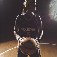 Dimly lit women holding basketball and standing on a basketball court in basketball uniform