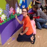 Smiling girl with glasses painting a mural