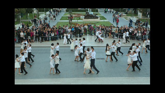 Dancers waltz together in an Armenian square