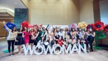 "Group of women pose in front of letters reading ""WoWoman"""
