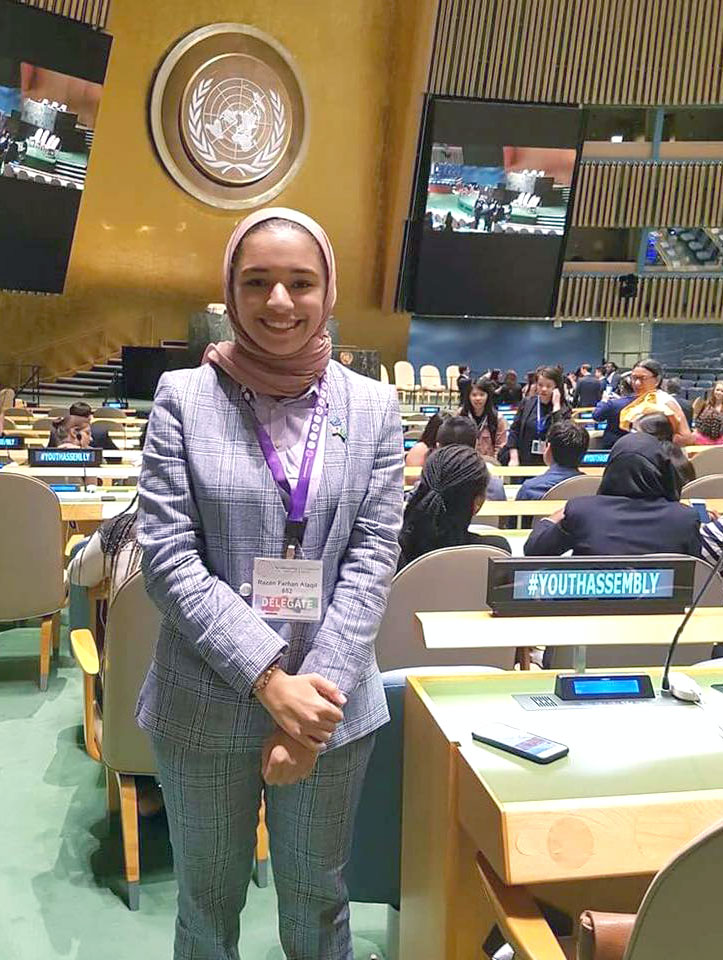Young woman wearing a headscarf and business suit smiling in the conference hall of the United Nations
