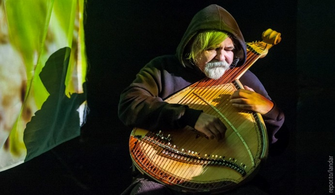 Older man playing a lute-like instrument