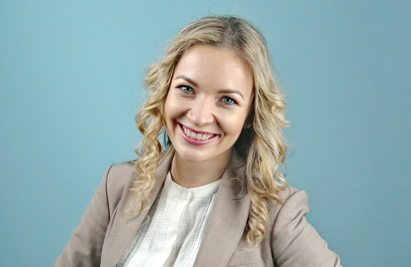 Young smiling Ukrainian woman with shoulder-length curly blond hair in beige blazer over a white nehru collared shirt.